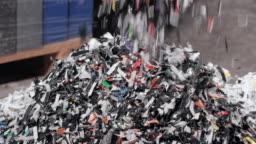 SLO MO Shredded plastic falling down from the conveyor belt