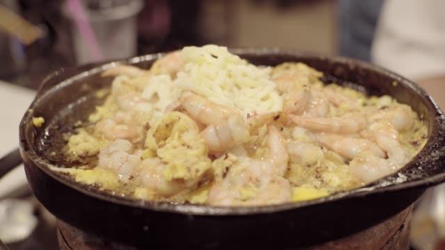 vidéos et rushes de crevettes et fromage dans une poêle. - parpaing