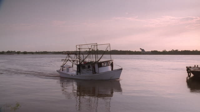 a shrimp boat flows along a dock on the mississippi river. - river mississippi stock videos & royalty-free footage