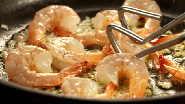 vídeos de stock, filmes e b-roll de ms shrimp scampi in skillet being sauteed in oil / los angeles, california, united states - frutos do mar