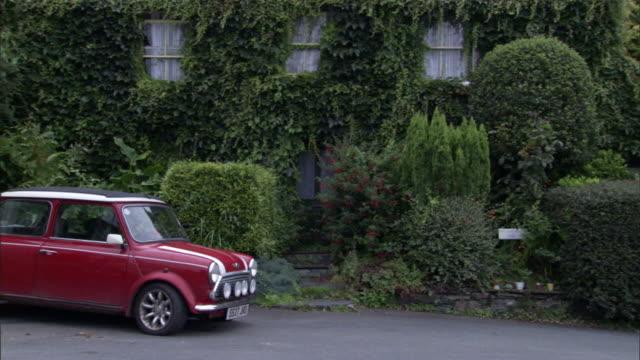 shrubbery and vines cover walls behind a mini cooper. - 自動車ブランド mini点の映像素材/bロール