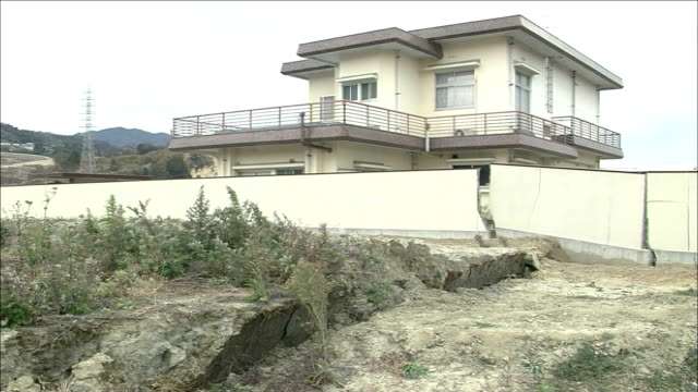 shrubs blow near a rift that broke a concrete wall during the hanshin earthquake in kobe, japan. - concrete wall stock videos & royalty-free footage