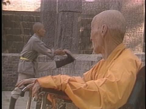 vídeos y material grabado en eventos de stock de shu dao sun watches as a young monk stretches his legs so he can practice kung fu at shaolin temple in the hunan province of china. - budismo