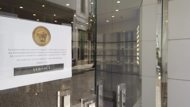 a shuttered versace store stands along the iconic and nearly empty rodeo drive on march 18 2020 in beverly hills california the city of beverly hills... - shutter stock videos & royalty-free footage