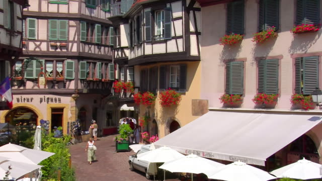 CU shutters on building and flowers hanging from window/ ZO HA WS people walking through Rue de Marchands in Petite Venise/ Colmar, France