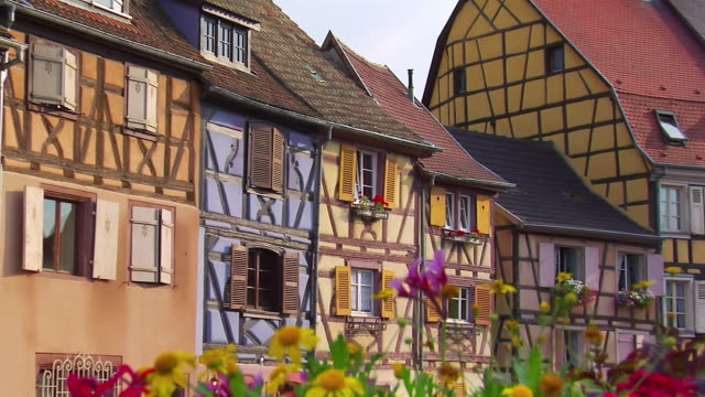 cu shutters on building/ zo ws people and traffic moving over rue de la poissonerie past colorful houses in petite venise/ colmar, france  - 男性と複数の女性点の映像素材/bロール
