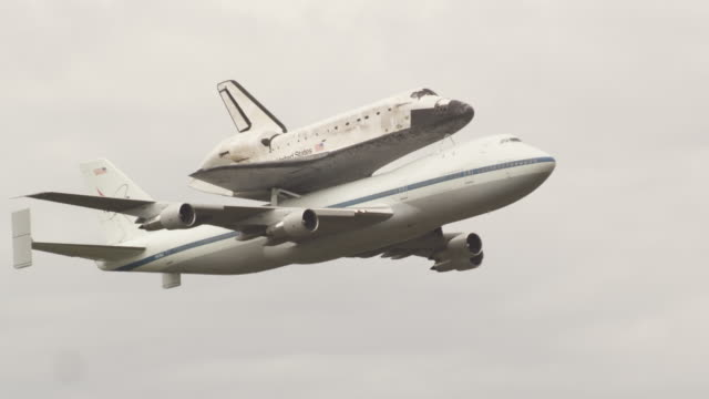MS NASA Shuttle Carrier Aircraft with Space Shuttle Discovery mounted atop flaying in gray cloudy sky / Sterling, Virginia, United States