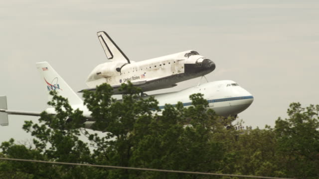 MS TS PAN NASA Shuttle Carrier Aircraft with Space Shuttle Discovery mounted atop disappears behind trees to landing at Dulles Airport / Sterling, Virginia, United States