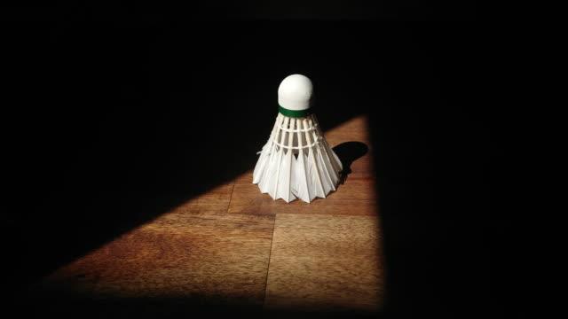 vídeos de stock, filmes e b-roll de badminton do peteca em uma tabela de madeira em um triengle da luz nos darknes - badmínton esporte