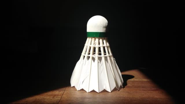 vidéos et rushes de badminton de volant sur une table en bois dans un triengle de lumière dans les darknes - badminton sport