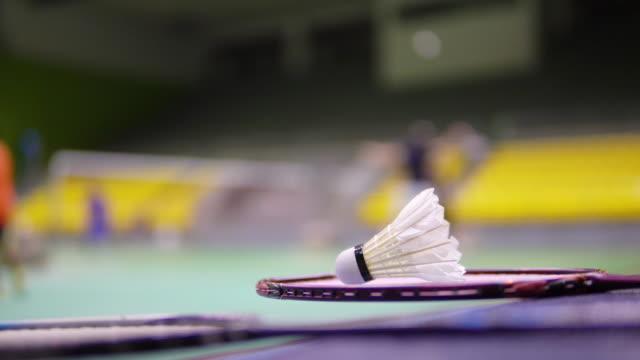vidéos et rushes de des volants sur le terrain de badminton avec des joueurs flous. - badminton sport