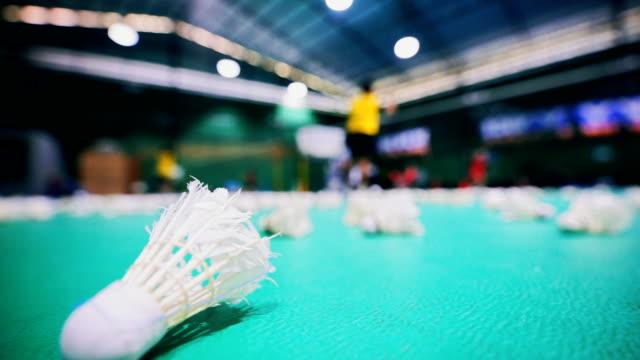vídeos de stock, filmes e b-roll de petecas na quadra de badminton com jogadores turva. - badmínton esporte