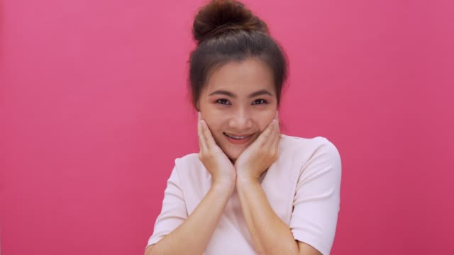 shy acting woman isolated pink background 4k - shy stock videos & royalty-free footage