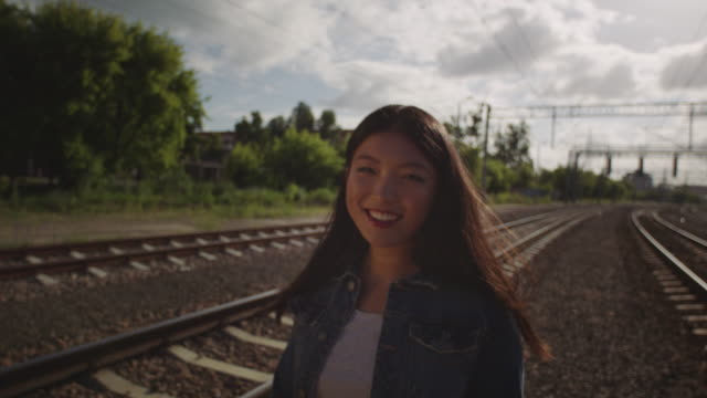 Shy Asian young woman alone on the railway.