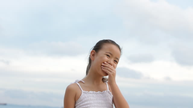 a shy chinese girl wearing a white pinafore enjoys making faces on the beach. - 6 7 years stock videos & royalty-free footage