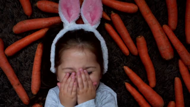 shy girl wearing a bunny ear costume and covering her face with her palms - shy stock videos & royalty-free footage