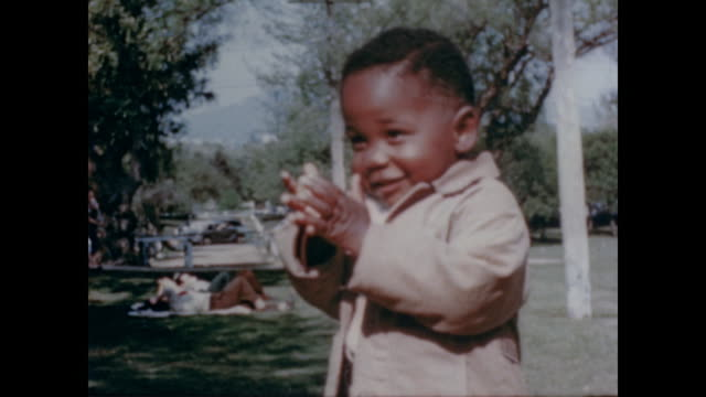 1947 shy toddler in park hides from camera - archival stock videos & royalty-free footage