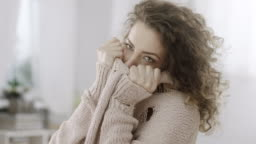Shy woman hiding her face in knitted sweater