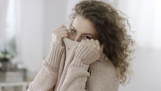 vídeos de stock, filmes e b-roll de mulher tímida que esconde sua face na camisola feita malha - esconder