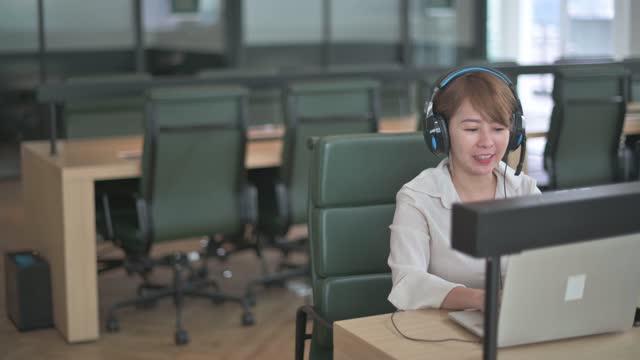 彼のビジネスパートナーとビデオ会議を呼び出すカメラビデオに話しているシアン中国の美しい女性ホワイトカラー労働者 - white collar worker点の映像素材/bロール