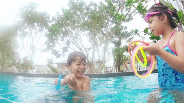 geschwister spielen im pool - schwimmflügel stock-videos und b-roll-filmmaterial