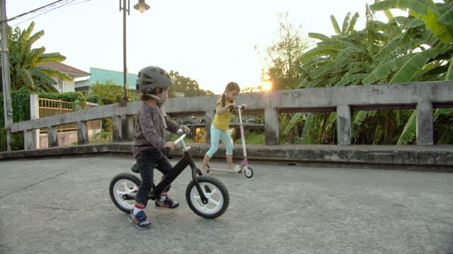 geschwister sind laufrad fahren. - fahrradhelm stock-videos und b-roll-filmmaterial