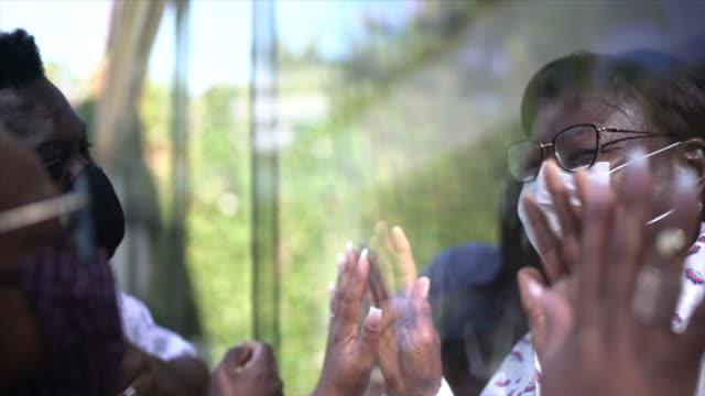 vídeos y material grabado en eventos de stock de hermano / pareja visitando madre en cuarentena, comunicándose a través de una ventana de cristal - adios