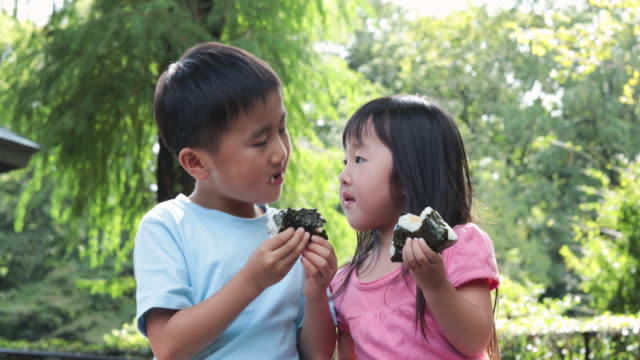 sibling eating a rice ball outdoors - rice ball stock videos & royalty-free footage