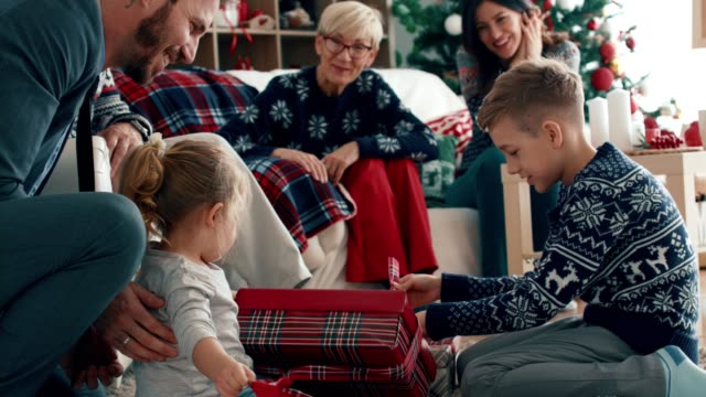 sibling opening their christmas gifts while - regalo di natale video stock e b–roll