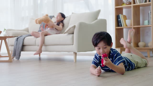 sibling playing with toys in living room,4k - lying on front stock videos & royalty-free footage