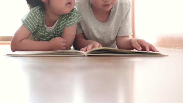 vidéos et rushes de frère de soeur affichant un livre à la maison - brightly lit