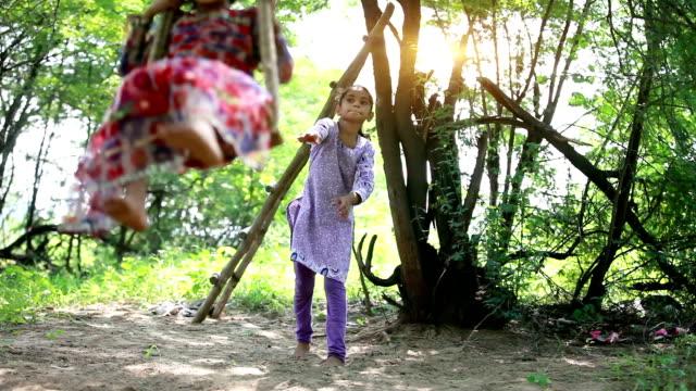 vídeos de stock e filmes b-roll de sibling sisters swinging on rope swing in an sunny day - equipamento de parque infantil