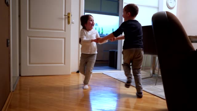 siblings at home spinning together and falling as a part of a game - children only stock videos & royalty-free footage