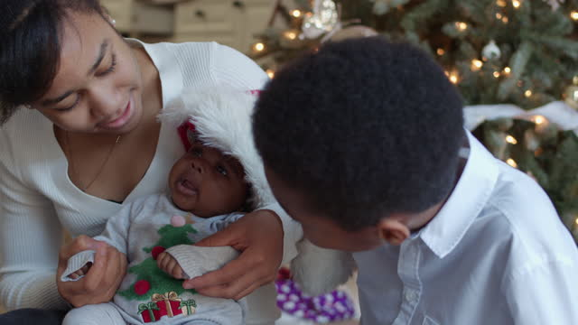 stockvideo's en b-roll-footage met broers en zussen genieten van kerstmis met hun nieuwe baby zus - cadeau