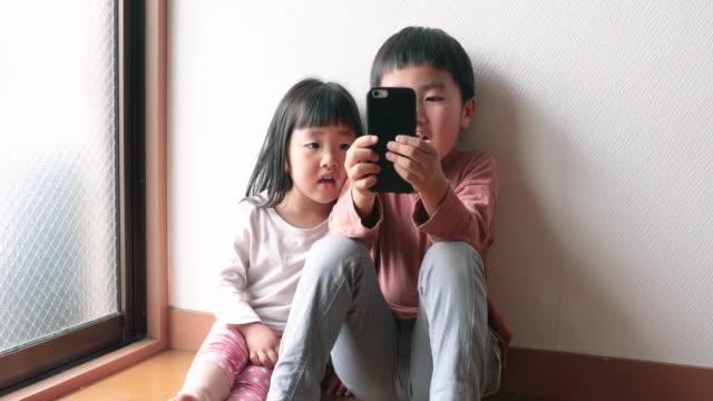 stockvideo's en b-roll-footage met broers en zussen genieten van videogesprek met smartphone thuis - brother