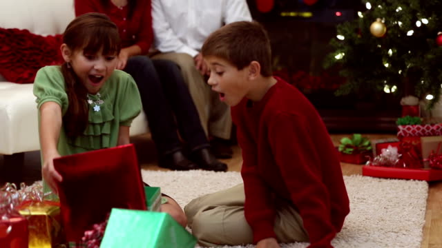 siblings excited with opening presents on christmas morning - christmas present stock videos and b-roll footage