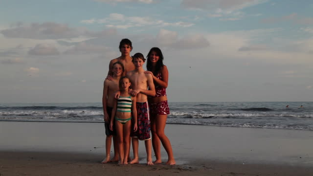 siblings flexing their muscles on the beach - sibling stock videos and b-roll footage