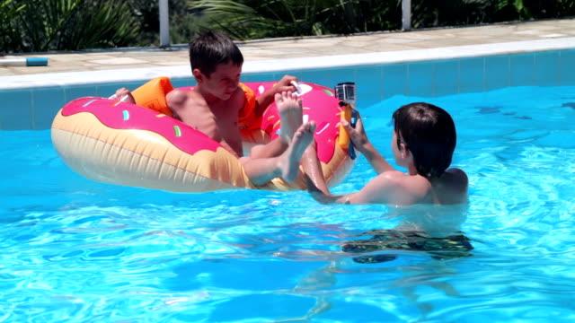 geschwister, die spaß in swimming poll, handheld erschossen - schwimmflügel stock-videos und b-roll-filmmaterial