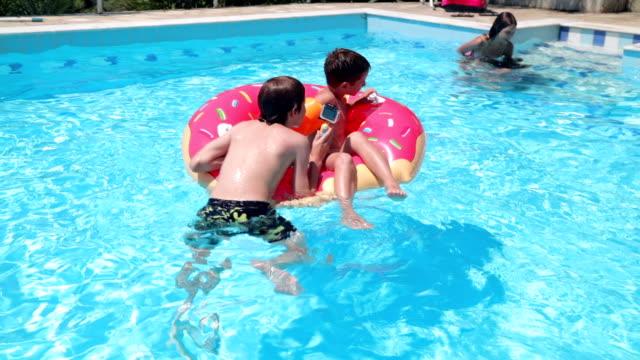 siblings having fun in swimming pool, handheld shot - capsizing stock videos and b-roll footage
