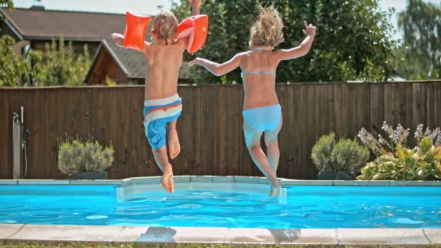 vidéos et rushes de ds frères et sœurs au ralenti en tenant les mains et sauter dans la piscine - clôture jardin