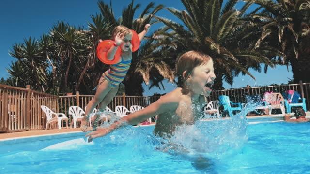 vidéos et rushes de frères et soeurs sautant dans la piscine au resort - station de vacances
