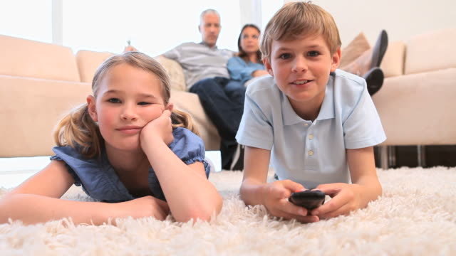 Siblings laughing while watching the television