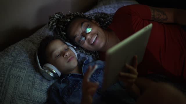 siblings listening music using digital tablet at bed - excitement stock videos & royalty-free footage
