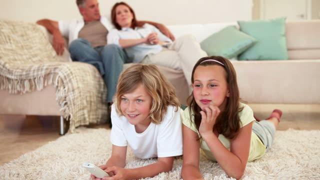 vídeos y material grabado en eventos de stock de siblings lying down while watching the television - tumbado boca abajo