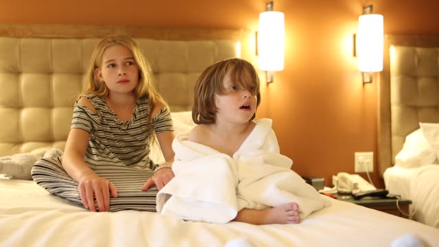 siblings on bed watching tv - piedi nudi bambine video stock e b–roll