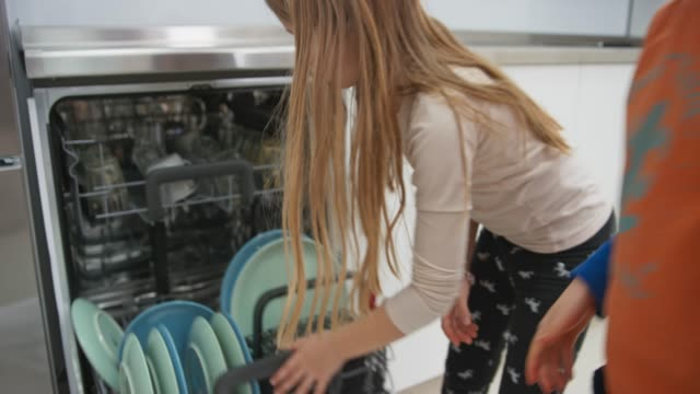 siblings placing glasses into the dishwasher and closing it - lavastoviglie video stock e b–roll