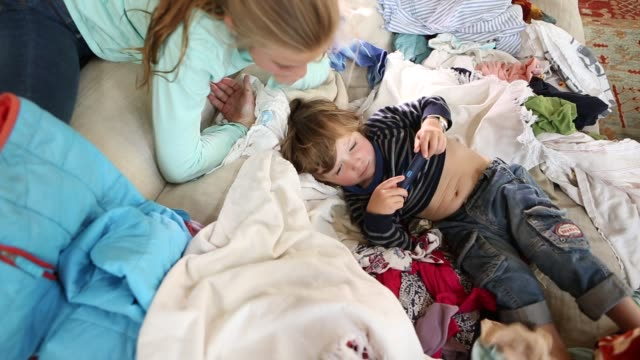 vidéos et rushes de siblings playing amid laundry - lessive corvée domestique
