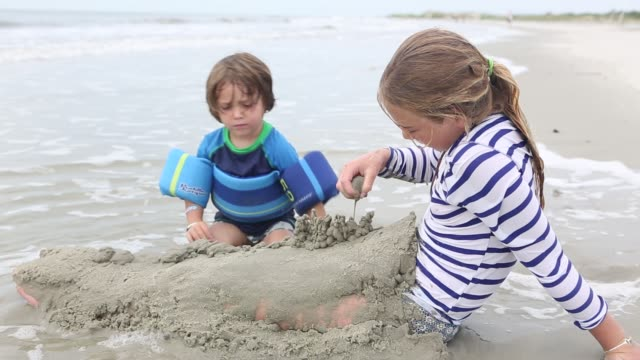 siblings playing at the beach
