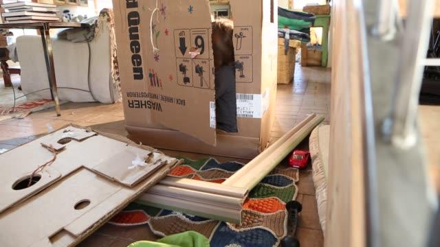 siblings playing in card board box in living room
