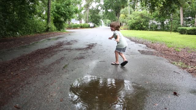 siblings playing in puddle - 4 5 anni video stock e b–roll